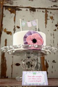 torta con fiore rosa e su alzata di vetro con cartoncino per buffet