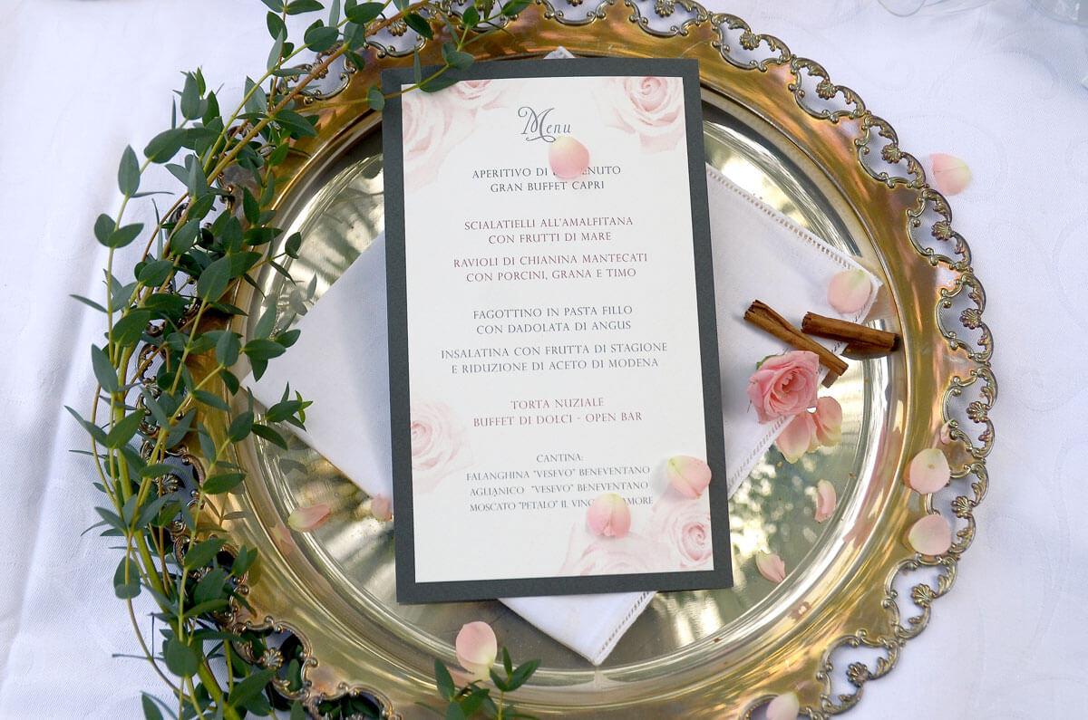 un menu per matrimonio su vassoio in argento e rose