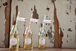 bottiglie di vetro con adesivi festa e cannucce con nome invitati