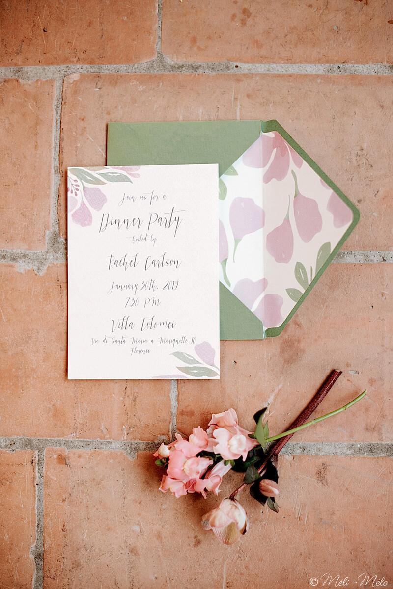 una partecipazione di matrimonio con busta foderata e fiori rosa