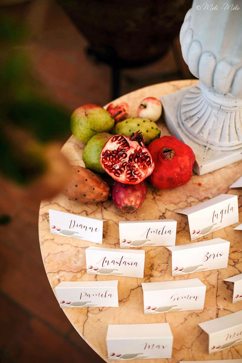 segnaposti a tema autunno su tavolino di marmo con fichi d'india melegrane e pere