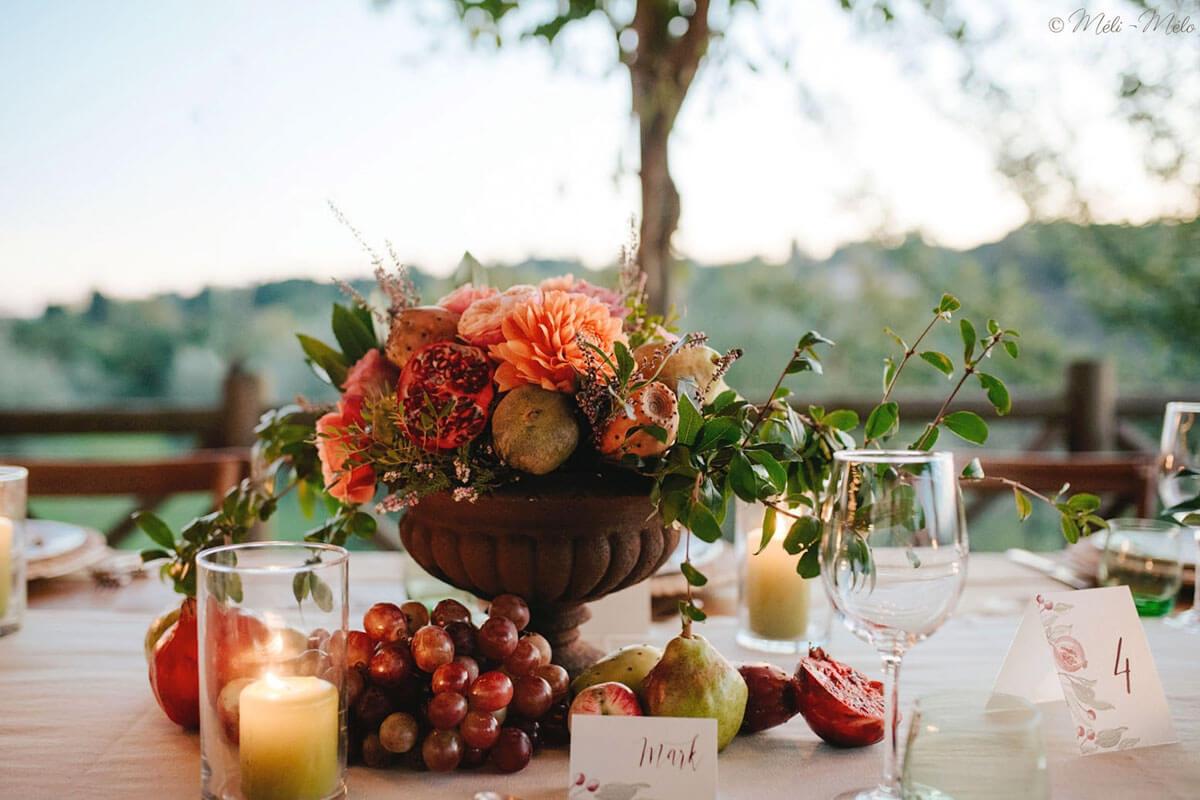 centrotavola composto di fiori e frutta autunnali e segnatavolo e segnaposto coordinati