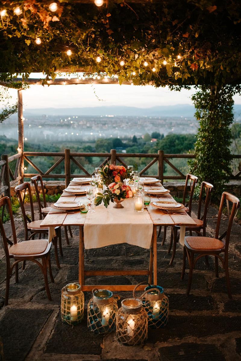 tavolo apparecchiato sotto un pergolato illuminato di lucine e lanterne