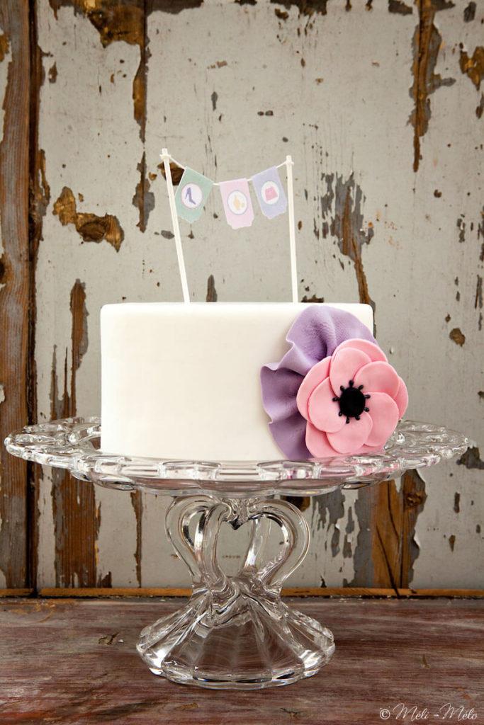 torta con fiore rosa e bandierine su alzata di vetro