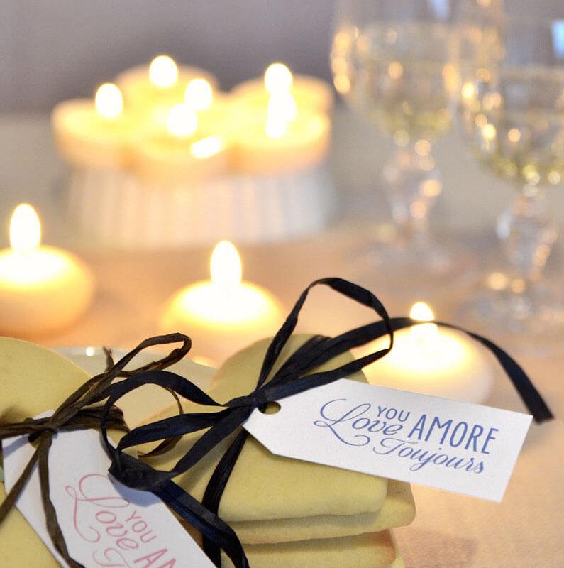 biscotti con etichette con scritte sull'amore su tavolo con candele e bicchieri