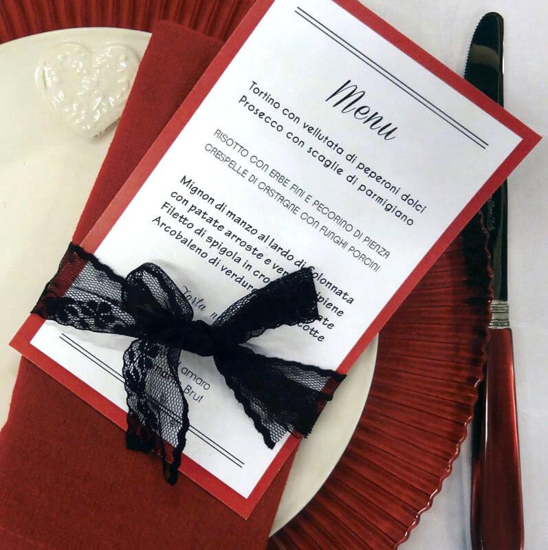 un menu di matrimonio su tavolo apparecchiato in rosso e nero
