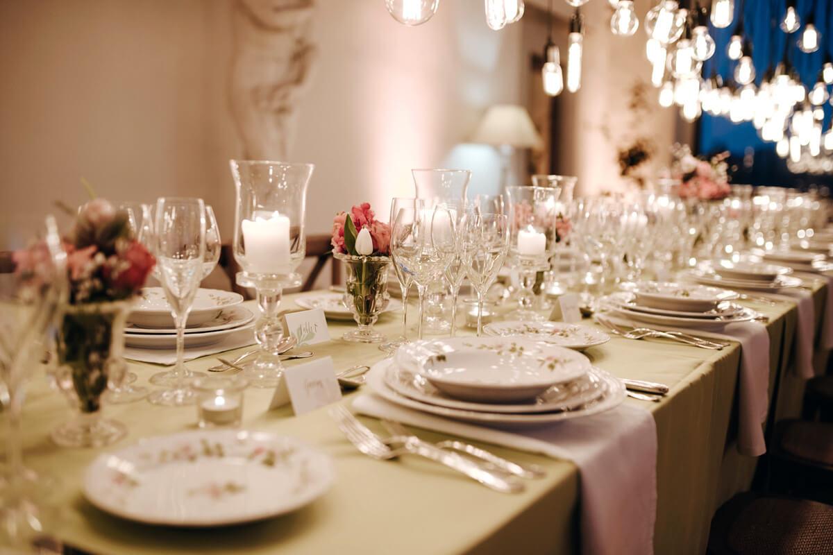 tavola apparecchiata con fiori candele e lampadine appese