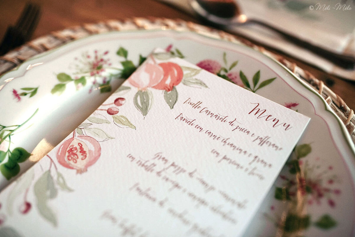 menu sopra un piatto con disegno di melegrane all'acquerello