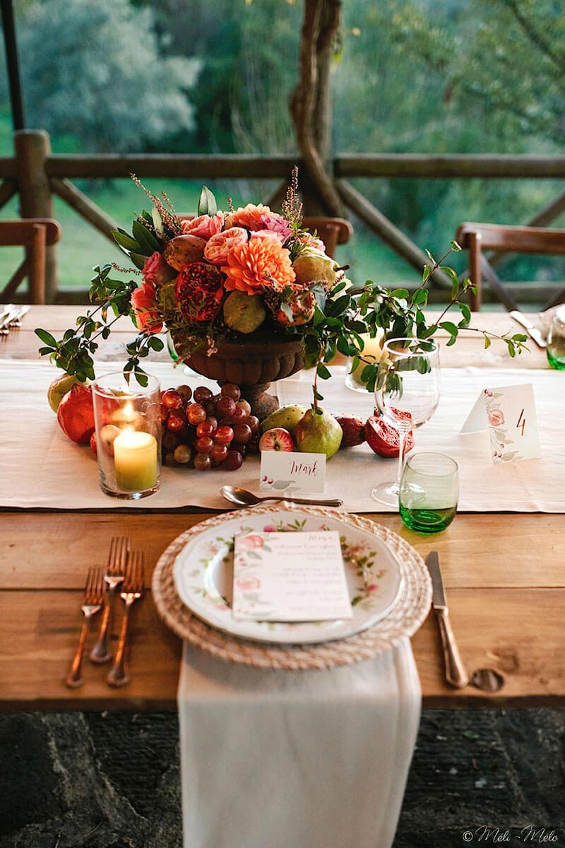 un tavolo apparecchiato con centrotavola composto di frutta e fiori autunnali